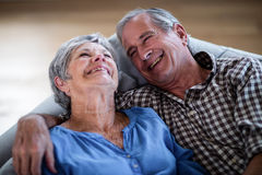 Happy senior couple relaxing on sofa and smiling Royalty Free Stock Photography
