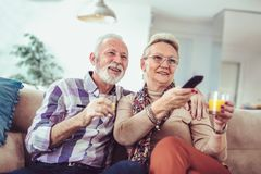 Happy senior couple with remote control watching tv royalty free stock image