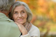 Close up portrait of happy senior couple resting in autumnal park royalty free stock photo