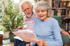 Happy Senior Couple Reviewing Finances At Home Stock Image