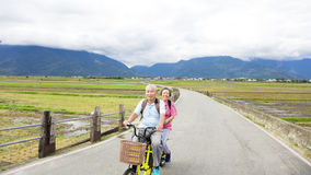 Happy Senior  Couple Riding Bicycle on country road Stock Images