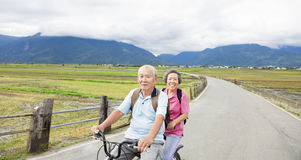 Happy Senior  Couple Riding Bicycle on country road Royalty Free Stock Photo