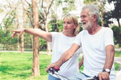 Happy senior couple riding a bicycle in the park. Happy elder couple riding a bicycle in the park stock photography