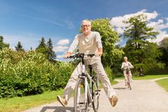 Happy senior couple riding bicycles at summer park Royalty Free Stock Images