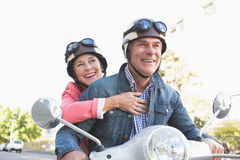 Happy senior couple riding a moped Stock Image