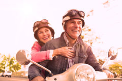 Happy senior couple riding a moped. On a sunny day Royalty Free Stock Image
