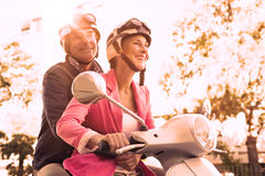 Happy senior couple riding a moped. On a sunny day Stock Photos
