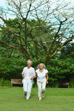 Happy senior couple running. Beautiful happy senior couple running  in green meadow Stock Photos