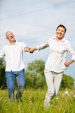 Happy senior couple running in summer. Over a grean meadow Stock Photos