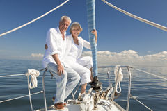 Happy Senior Couple on a Sail Boat. A happy senior couple sitting at the bow of a sail boat on a calm blue sea Stock Photography