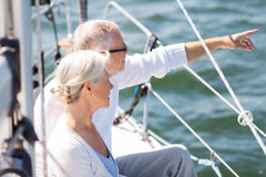 Happy senior couple on sail boat or yacht in sea stock photos