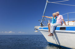 Happy Senior Couple Sailing on a Sail Boat. A happy senior couple sitting on the side of a sail boat on a calm blue sea looking and pointing to a clear horizon Royalty Free Stock Image