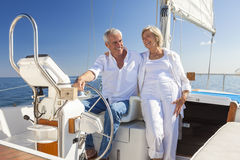 Happy Senior Couple Sailing Yacht or Sail Boat. A happy senior couple laughing having fun sailing at the wheel of a yacht or sail boat on a calm blue sea Royalty Free Stock Photos