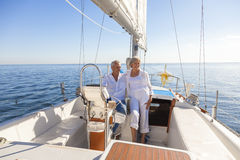 Happy Senior Couple Sailing Yacht or Sail Boat. A happy senior couple laughing having fun sailing at the wheel of a yacht or sail boat on a calm blue sea Stock Images