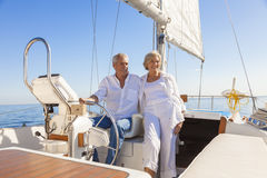 Happy Senior Couple Sailing Yacht or Sail Boat. A happy senior couple laughing having fun sailing at the wheel of a yacht or sail boat on a calm blue sea Stock Photo