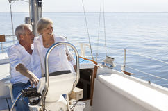 Happy Senior Couple Sailing Yacht or Sail Boat. A happy senior couple sailing and sitting at the wheel of a sail boat on a calm blue sea Stock Image