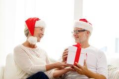 Happy senior couple in santa hats with gift box Royalty Free Stock Photography