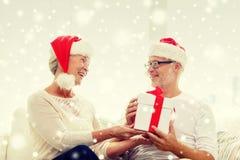 Happy senior couple in santa hats with gift box Stock Photo