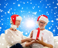 Happy senior couple in santa hats with gift box Royalty Free Stock Photos