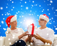 Happy senior couple in santa hats with gift box Royalty Free Stock Images