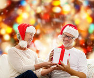 Happy senior couple in santa hats with gift box Royalty Free Stock Photo