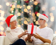 Happy senior couple in santa hats with gift box Royalty Free Stock Photography