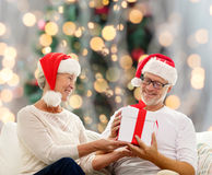 Happy senior couple in santa hats with gift box Royalty Free Stock Image