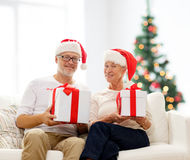Happy senior couple in santa hats with gift boxes Royalty Free Stock Images