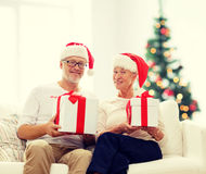Happy senior couple in santa hats with gift boxes Stock Images