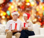 Happy senior couple in santa hats with gift boxes Royalty Free Stock Photos