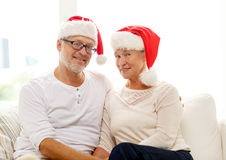 Happy senior couple in santa helper hats at home Royalty Free Stock Image