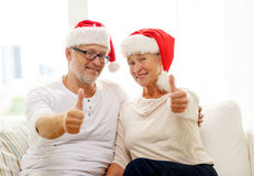 Happy senior couple in santa helper hats at home Royalty Free Stock Photography