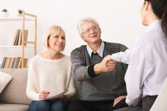 Happy senior couple sealing contract with financial advisor royalty free stock photos