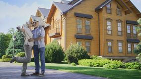 Happy senior couple showing keys to new big house stock footage