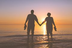 Happy senior couple silhouettes on the beach. Senior couple holding hands on a background a beautiful sunset and walk on water Royalty Free Stock Image