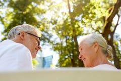 Happy senior couple sitting on bench at park Royalty Free Stock Image