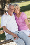 Happy Senior Couple Sitting on Bench in Sunshine Stock Photo