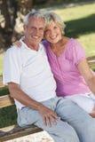 Happy Senior Couple Sitting on Bench in Sunshine Stock Photo