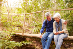 Happy senior couple sitting on bridge in forest, horizontal Stock Photos