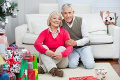 Happy Senior Couple Sitting By Christmas Presents Stock Images