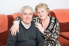 Happy senior couple sitting close together stock photography
