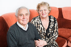 Happy senior couple sitting close together on a sofa Royalty Free Stock Image