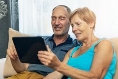 Happy senior couple sitting on couch and using digital tablet Stock Image