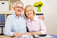 Happy senior couple sitting at desk Royalty Free Stock Photos