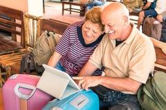 Happy senior couple sitting with digital laptop during at travel trip. Happy senior couple sitting with digital laptop and travel baggage during adventure trip Royalty Free Stock Photos