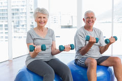 Happy senior couple sitting on fitness balls with dumbbells Royalty Free Stock Photos
