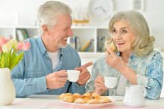 Senior couple drinking tea with cookies. Happy senior couple sitting at kitchen table and drinking tea with cookies Royalty Free Stock Image