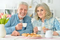 Senior couple drinking tea with cookies. Happy senior couple sitting at kitchen table and drinking tea with cookies Stock Photo
