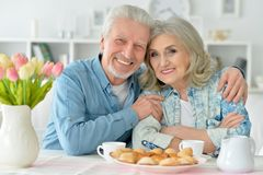 Senior couple drinking tea with cookies. Happy senior couple sitting at kitchen table and drinking tea with cookies Royalty Free Stock Photo