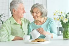 Happy senior couple sitting at kitchen table and drinking tea. With cookies Royalty Free Stock Images